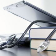Medical stethoscope and laptop and books