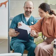 Vet talking with dog owner in the clinic
